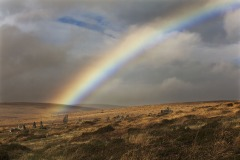 A rainbow above Scorhill Rocks, standing stones on Scorhill Down, nr Chagford, Dartmoor National Park, Devon, Great Britain.