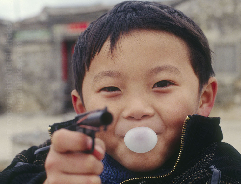 Young boy with bubble gum and toy guny, one image in Nigel Hicks's Goals in Photography talk.